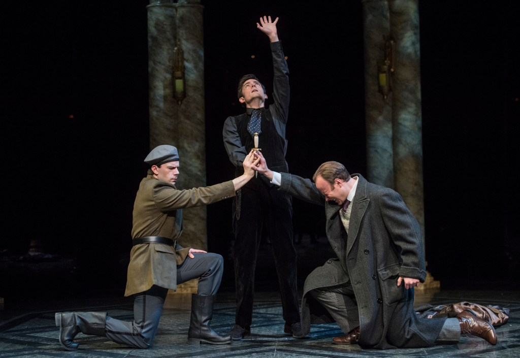 Hamlet (Matthew Amendt) swears Marcellus (Patrick Cannon, L.) and, Horatio (Andrew William Miller, R.) to silence with his knife.