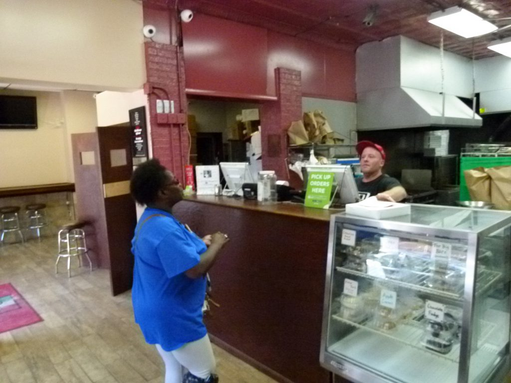 Keith Schrum rings up a take-out pizza order for a customer at Larry & Carol's.