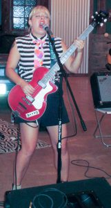 Jenn Jannon-Fischer sings to the back row while playing the bass guitar.