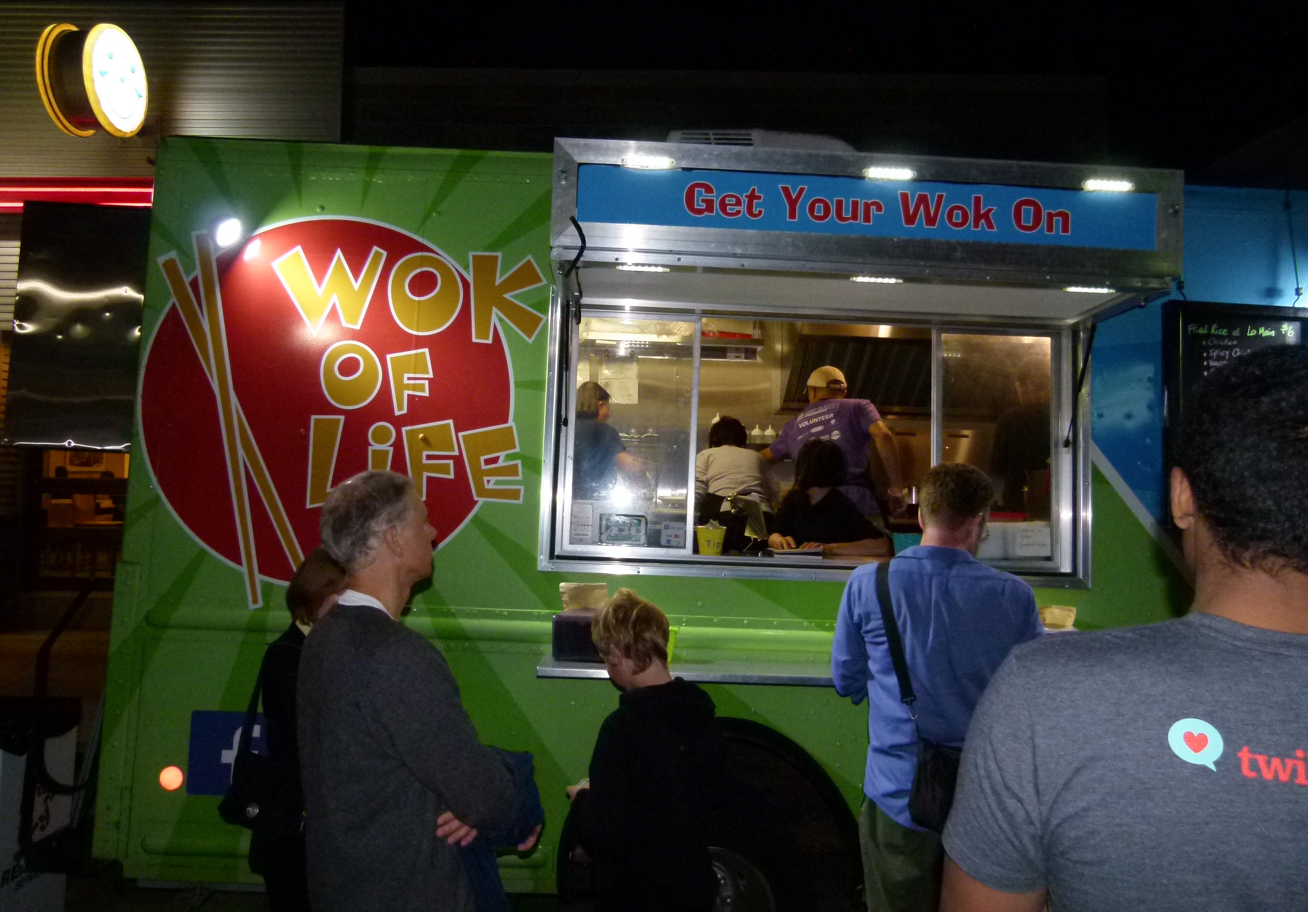 The crew at Wok of Life food truck rapidly preparing hungry patrons' orders as the Eat'n Park lighted Smiley Cookie sign illuminates from above.