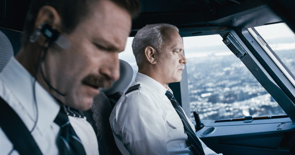 "Captain ""Sully"" Sullenberger (Tom Hanks) keeps a steady eye on the situation while first officer Jeff Skiles (Aaron Eckhart) checks the emergency handbook."