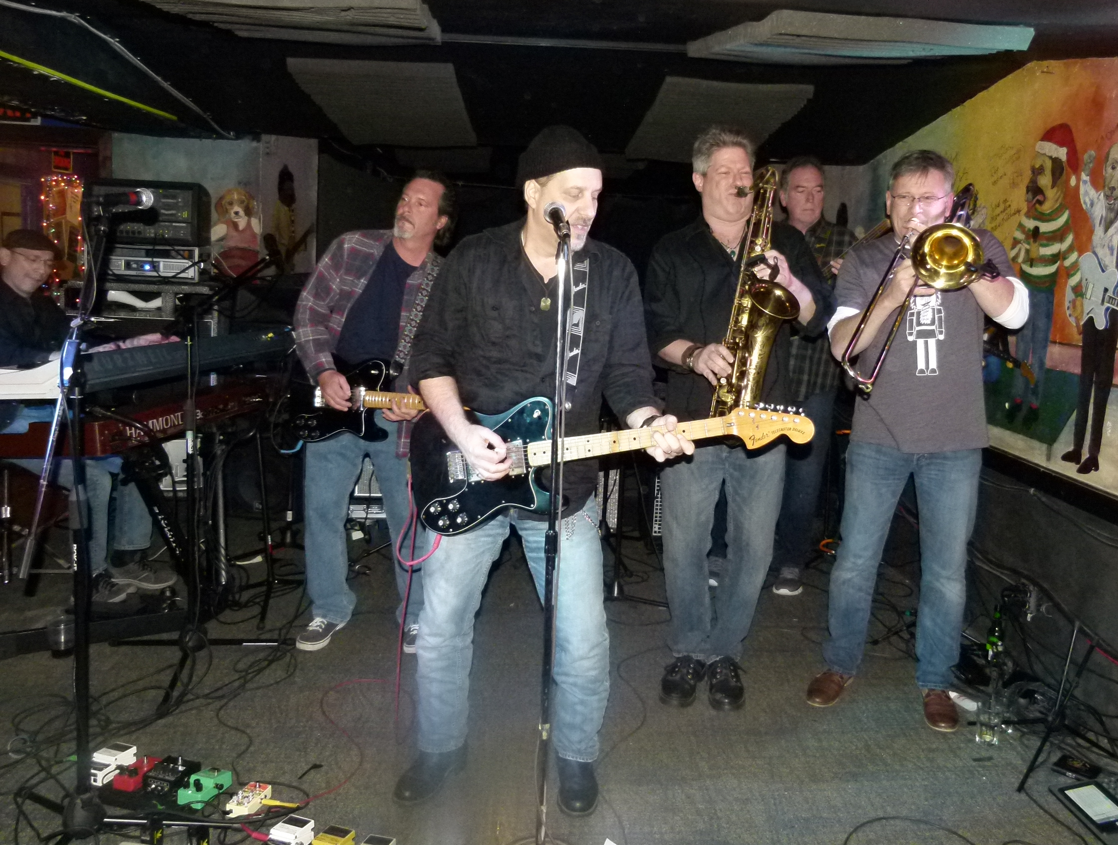 Bill Toms plays some killer lead guitar riffs (c.) while Hard Rain and the Soulville Horns jam on.