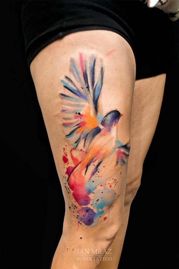 the painted bird tattoo on thigh