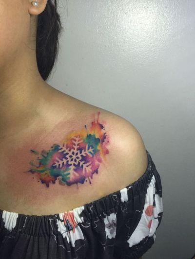 watercolor snowflake tattoo on collarbone
