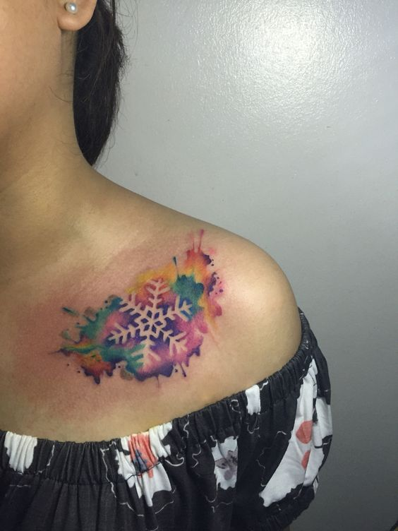 watercolor snowflake tattoo on collarbone