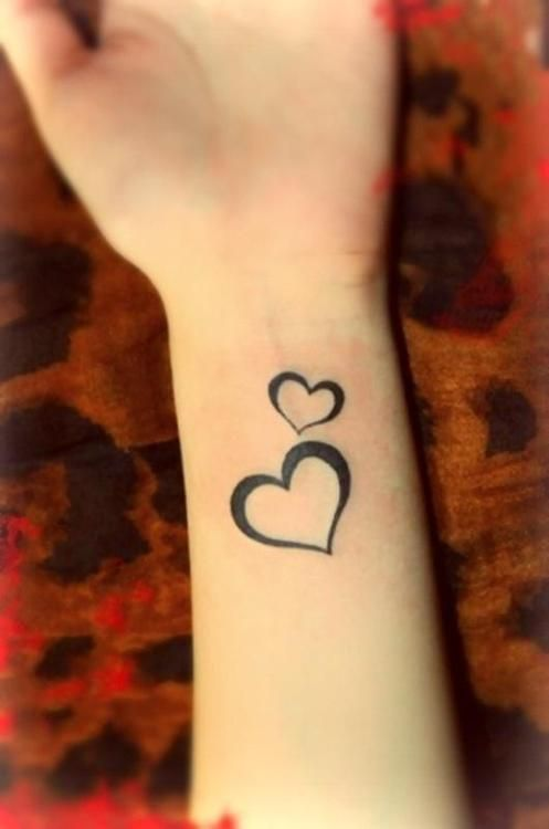 small outlined hearts inked tattoo on wrist