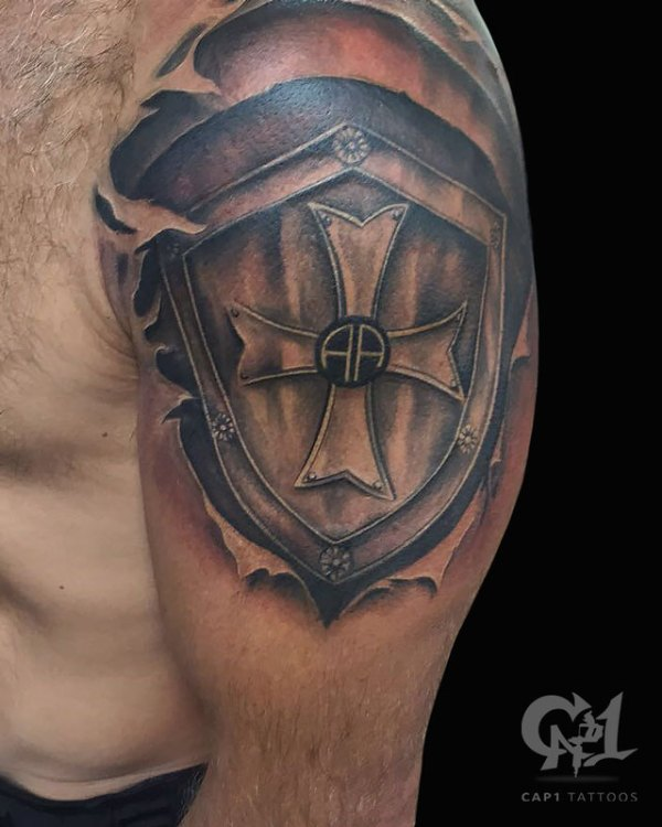 shoulder armor shield tattoo on upper sleeve