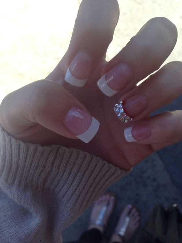 white french tip nails with diamonds on ring finger