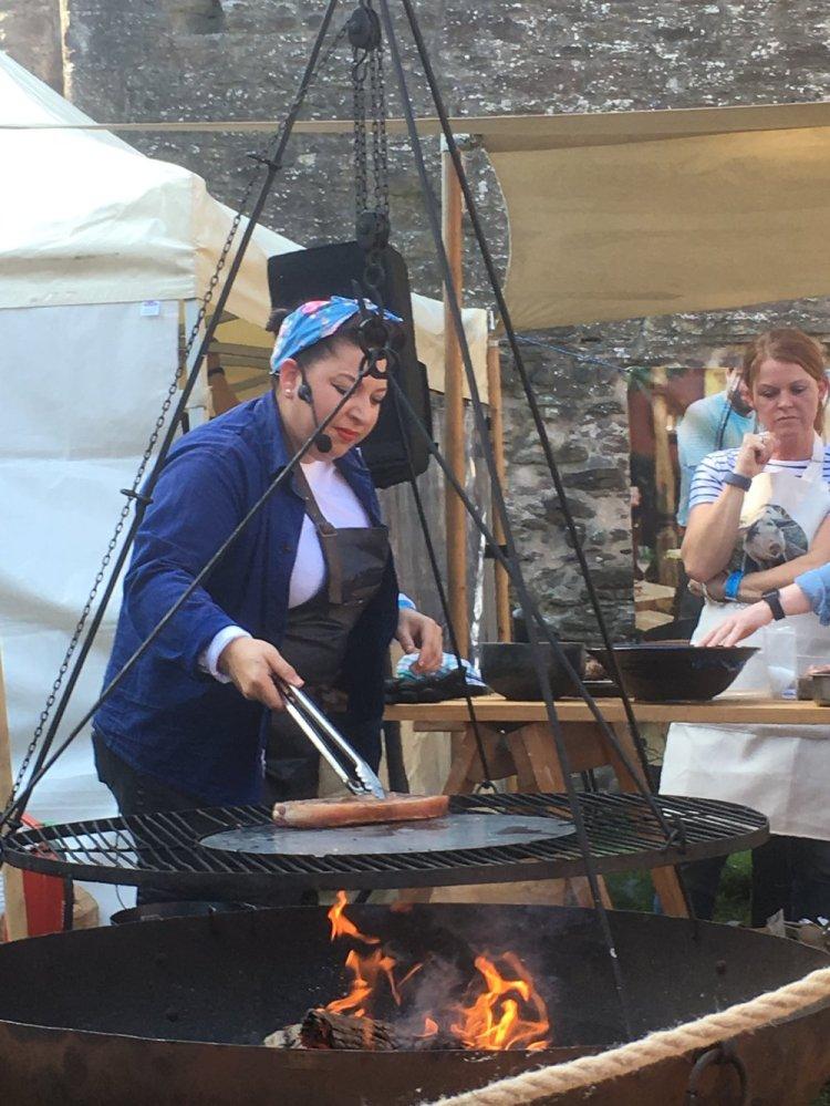 Hang Fire's Sam Evans prepares some pork at Abergavenny Castle. Photo: Entertainment South Wales