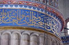 Arabic text from the Q'uran forms a frieze around the top of a massive main column