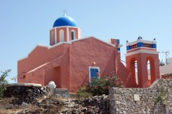 wide view of a church with a blue dome, but with pink walls instead of white