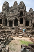 Wide view of semi-ruined Khmer temple at Bayon with face towers