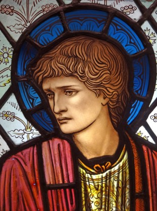 Close up of stained glass head of St Paul designed by Edward Burne-Jones