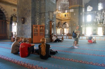 People sitting on the carpet inside the New Mosque in Istanbul