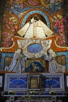 The Black Madonna shrine, with the statue of the Madonna dressed in a cream robe surrounded by frescoes and mosaics