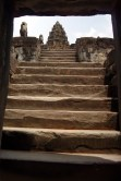 view from the bottom looking up the steep flights of stairs leading to the central tower at the top of Bakong temple