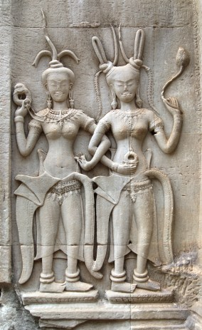These devatas have very elaborate hairstyles rather than formal head-dresses. The one on the right is holding up a lotus bud, the model for the shape of the stone towers of Angkor Wat.