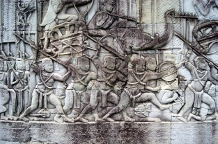 Khmer warriors charging into battle, trampling the dead bodies of their Cham (Vietnamese) enemies. Their generals ride on battle elephants behind.