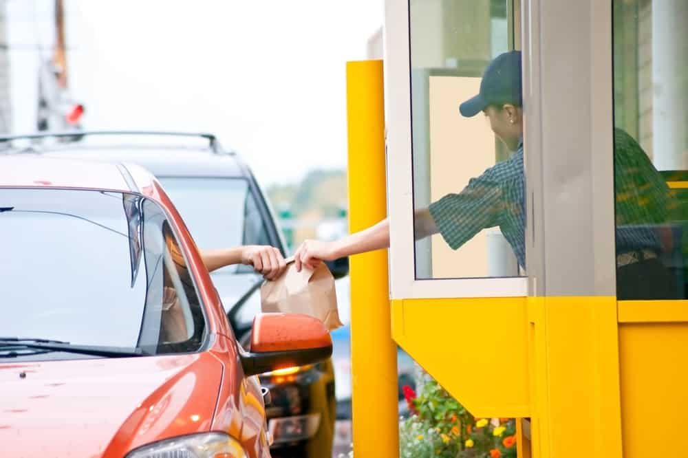Food is handed through the drive through window at a fast food restaurant