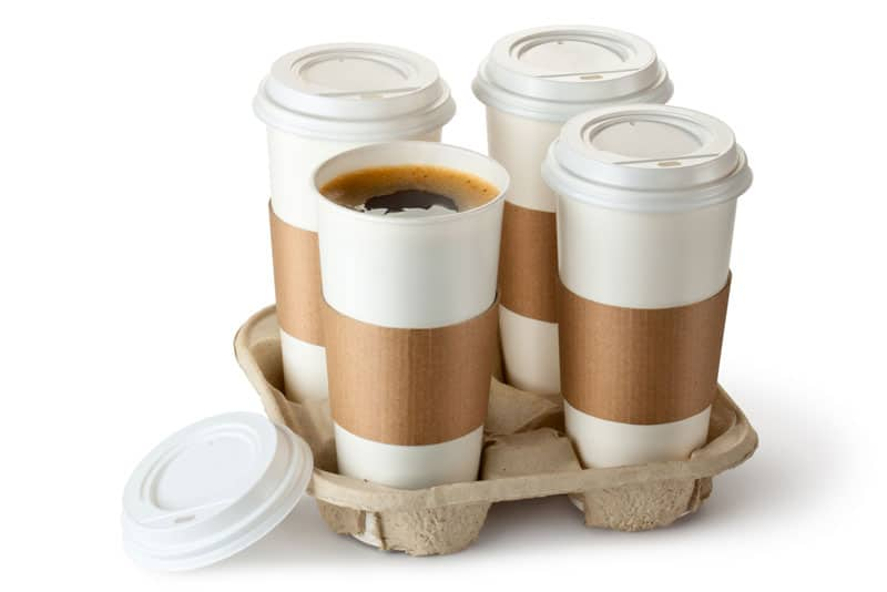 "Picture of a cheap pressed paper cup holder holding four cups of coffee,, with the caption ""We look at the best drink holders that Doordash Uber Eats Grubhub and Postmates contractors can use (and no, this is not one of them)"""