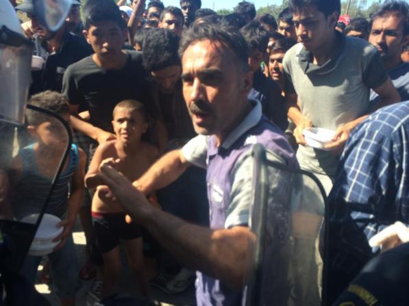 Refugiado sirio se enfrenta a los agentes antidisturbios para conseguir un plato de comida en un campo improvisado en Mitilini. / S. Rodrigo