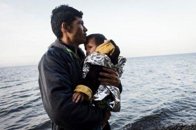 © UNHCR/Achilleas Zavalli – Tras cruzar el mar Egeo desde Turquía en una barca hinchable llena de refugiados afganos, un joven refugiado afgano, con su hijo en brazos, mira al mar después de llegar sano y salvo a las costas de la isla de Lesbos.