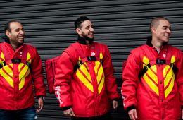 Três entregadores do iFood com jaqueta e bags