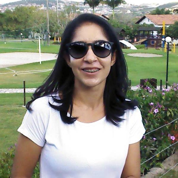 Ela tem a pele branca, cabelos lisos e pretos na altura dos ombros. Usa óculos de sol redondo e tem aparelho dentário, sorri. Ela traja camisa branca. Atrás dela, há um gramado.