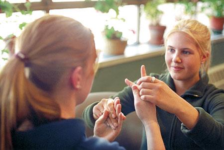 Intérprete loira segura as mãos de uma mulher à frente