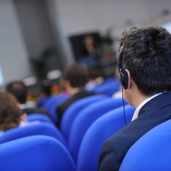 Sentado de costas para nós, um homem usa fones de ouvido. À frente dele há outras pessoas sentadas em poltronas azuis.