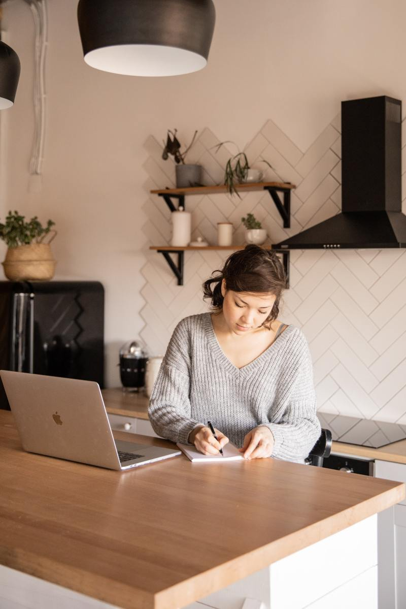 There's a girl in a kitchen with a MacBook in front of her, and she's writing her ideas for a business plan on a notepad. She's wearing a gray sweater and she has white skin. The kitchen have black and white details.