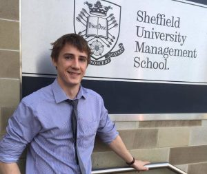 picture of Ben Pinder standing in front of a Sheffield University Management School sign