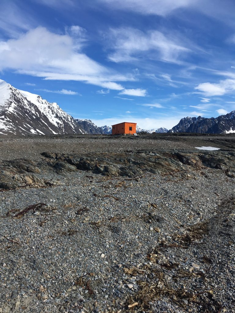 A small orange cabin located on a rocky Arctic beach
