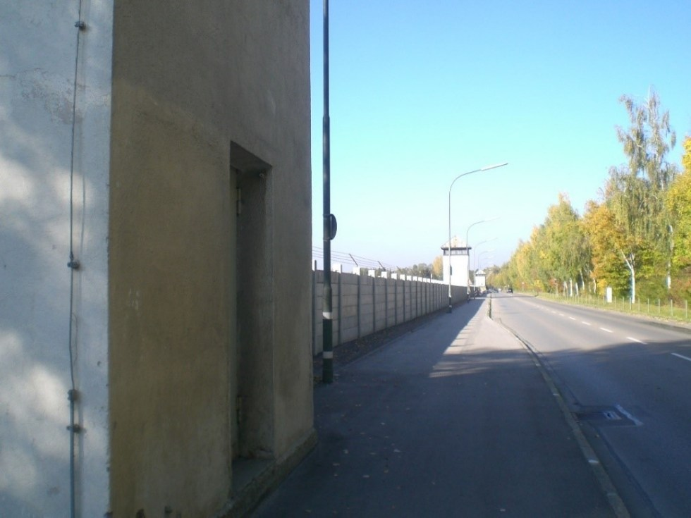 A paved road lined by a barbed-wire-topped wall