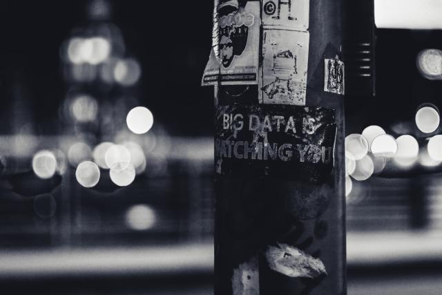 Street-level poster advertising on a street light, one reading BIG DATA IS WATCHING YOU.