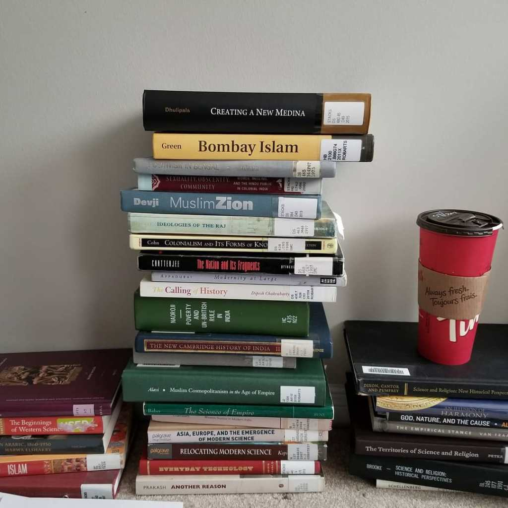 An image of books from an academic exam list and a cup from Tim Hortons