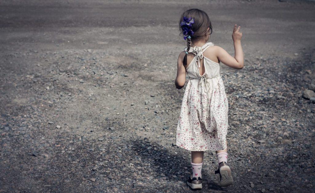 Flicka 4 år gör peace-tecken på grusväg.
