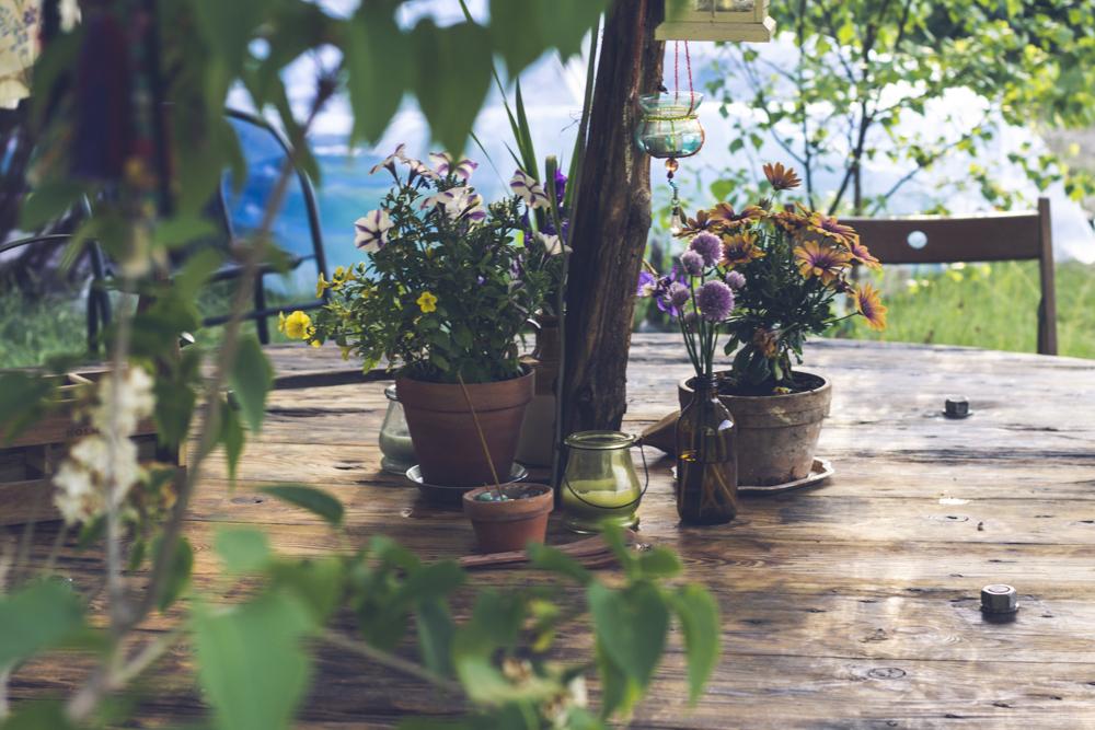 Midsommar utomhus med pyntat bord och regnskydd.