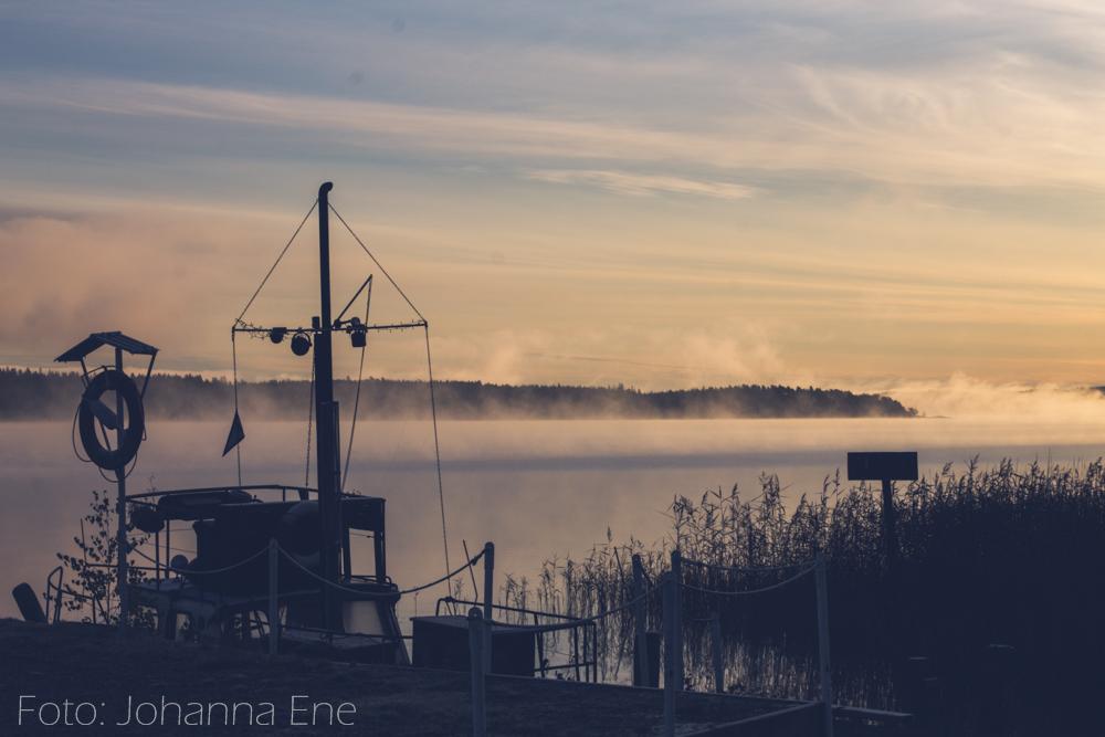 Båt vid brygga en tidig morgon med dimma över sjö.