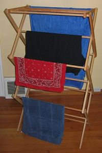 An image showing a collapsible wooden drying rack with clothes hanging to dry.