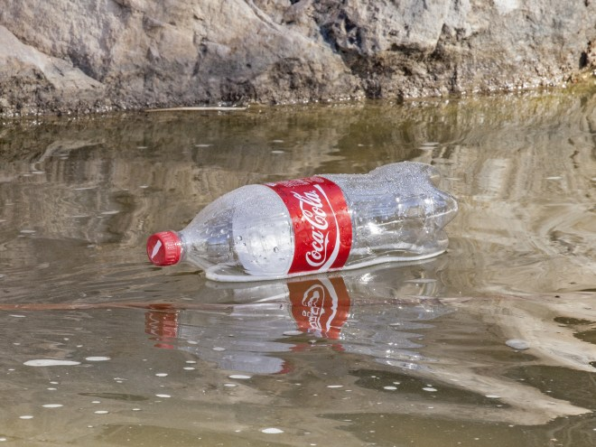 Plastic Coca-Cola bottle floating in water