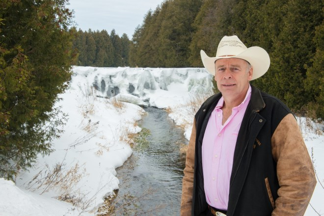 Cattle rancher Carl Cosack stands in front of a river in Melancthon Township.