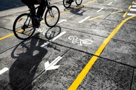 Cyclists following a Cycle track on street. Beautiful sunny day with two cyclist with shadows on cycle track.