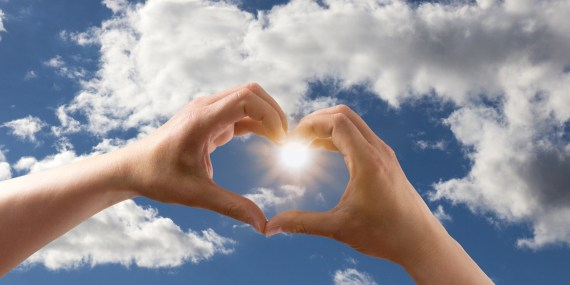 Heart shaped hands with cloud in the sky