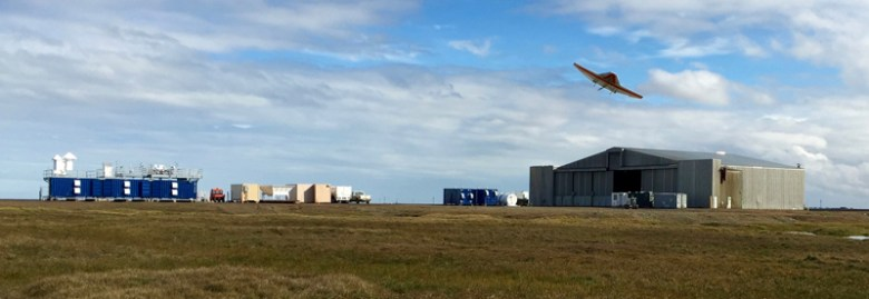 A DataHawk UAS (1-meter wingspan) completes low-altitude flights at Oliktok Point during the Evaluation of Routine Atmospheric Sounding Measurements using Unmanned Systems (ERASMUS) campaign, with the mobile research facility AMF-3 in the background. Credit: Gijs de Boer.
