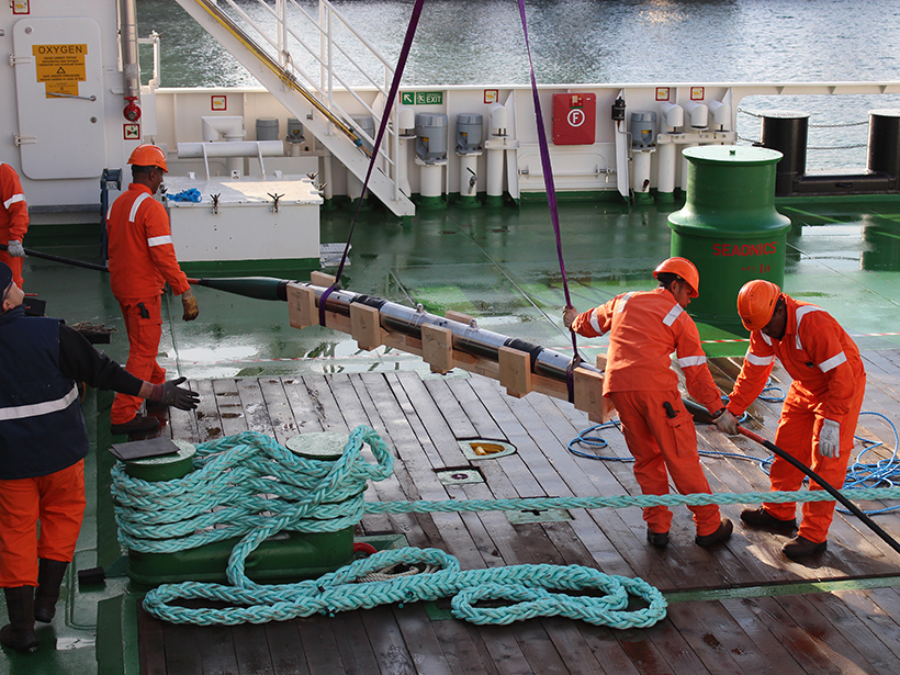 Crew members load an optical repeater during the deployment of a submarine telecommunications cable system.