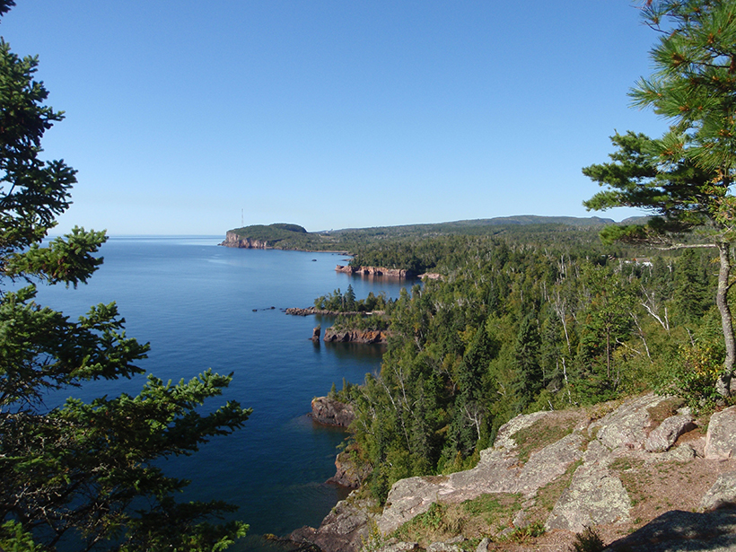Cliffs of 1.1-billion-year-old volcanic rocks from the Midcontinent rift in Tettegouche State Park, Minnesota tower above the brilliant blue waters of Lake Superior.