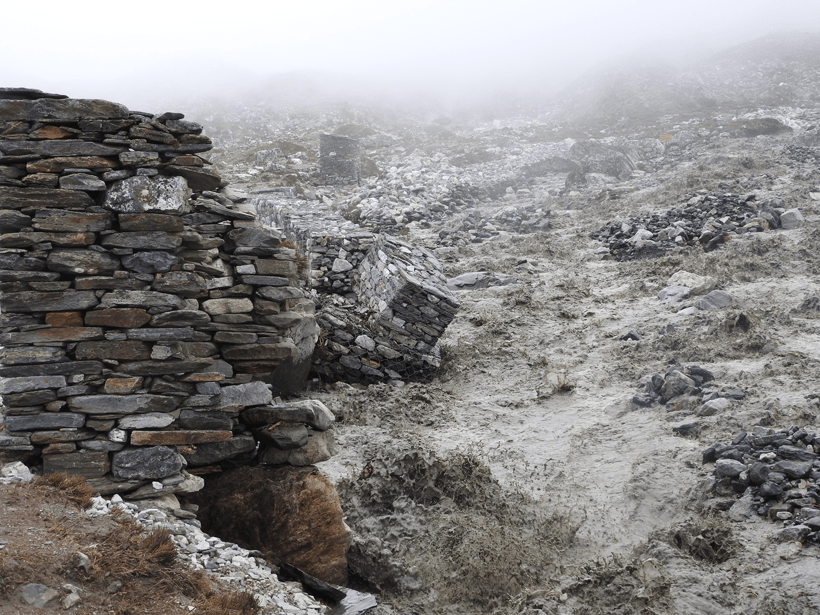 A glacial outburst flood from Lhotse Glacier on 12 June 2016 threatens a stone wall adjacent to a village in Nepal.