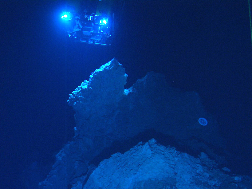 The spotlights of a remotely operated vehicle illuminate carbonate rock spires of the Lost City hydrothermal vent field in the Atlantic Ocean.