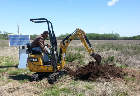 A member of the Kansas Geological Survey field crew installs a seismic station in south central Kansas.